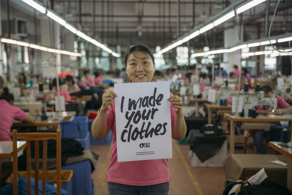 A Picture Organic garment worker holding a sign that says I made your clothes