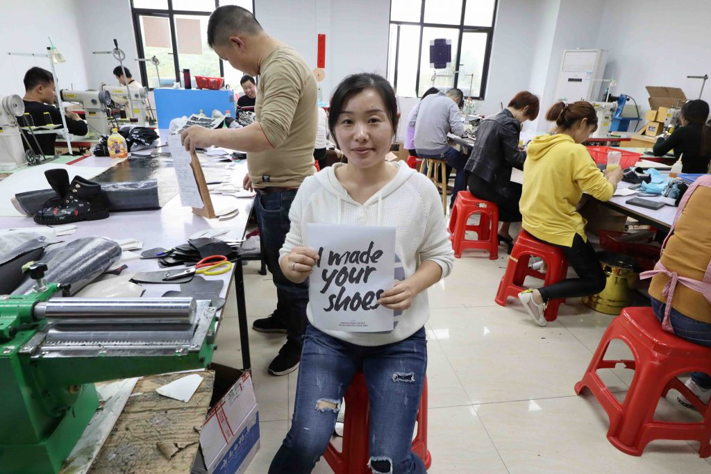 """A shoe maker holding a sign saying """"I made your shoes"""""""